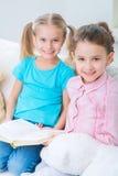 Petites soeurs gaies s'asseyant sur le sofa Images libres de droits