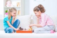 Petites soeurs gaies s'asseyant sur le sofa Photo libre de droits