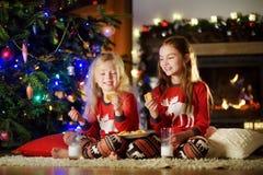 Petites soeurs heureuses ayant le lait et des biscuits par une cheminée dans un salon foncé confortable le réveillon de Noël Images libres de droits