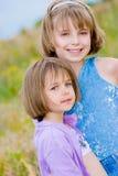 Petites soeurs heureuses sur le fond vert de pré Images stock