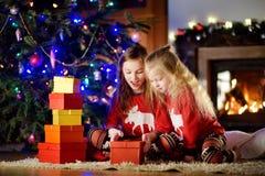 Petites soeurs heureuses utilisant des pyjamas de Noël jouant par une cheminée dans un salon foncé confortable le réveillon de No Photo libre de droits