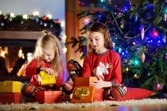 Petites soeurs heureuses utilisant des pyjamas de Noël jouant par une cheminée dans un salon foncé confortable le réveillon de No Photographie stock