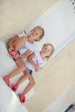 Petites soeurs mignonnes s'asseyant près de la vieille maison dedans Images libres de droits