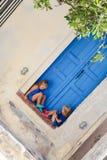 Petites soeurs mignonnes s'asseyant près de la vieille porte bleue dedans Photographie stock