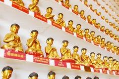 Petites statues d'or de Bouddha à l'intérieur des dix-millièmes Photographie stock