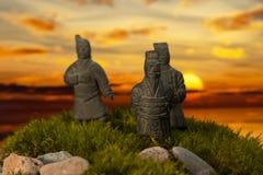 Petites statues sur la mousse au coucher du soleil Images stock