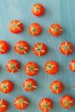 Petites tomates-cerises sur un bleu en bois Photos stock