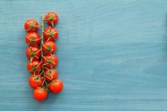 Petites tomates-cerises sur un bleu en bois Photographie stock