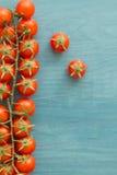 Petites tomates-cerises sur un bleu en bois Photographie stock libre de droits