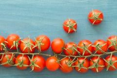 Petites tomates-cerises sur un bleu en bois Image stock