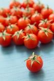 Petites tomates-cerises sur un bleu en bois Images stock
