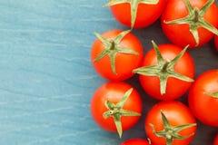 Petites tomates-cerises sur un bleu en bois Photo stock