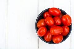 Petites tomates mûres rouges dans la cuvette sur la table en bois, vue supérieure Photos stock