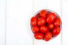 Petites tomates mûres rouges dans la cuvette sur la table en bois, vue supérieure Image stock