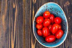 Petites tomates mûres rouges dans la cuvette sur la table en bois, vue supérieure Images stock