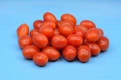 Petites tomates rouges sur un fond bleu Images stock