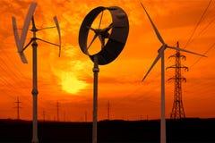 Petites turbines de vent dans le coucher du soleil images libres de droits