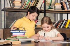 Petits écoliers étudiant dans la bibliothèque ensemble Images stock