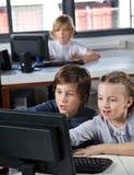 Petits écoliers regardant le moniteur d'ordinateur Images libres de droits