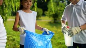 Petits écologistes amicaux travaillant dans l'équipe tout en nettoyant en parc banque de vidéos