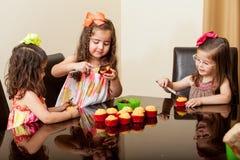 Petits amis faisant des petits gâteaux cuire au four Photographie stock