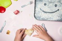 Petits bébé moulage à main le coeur d'une pâte faite maison Smiley sur un plateau de farine photographie stock libre de droits
