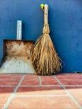 Petits balai et pelle à poussière sur un fond bleu de mur Photo libre de droits