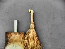 Petits balai et pelle à poussière sur un fond gris de mur Photo libre de droits