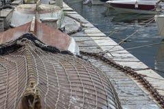Petits bateaux couverts de filet de pêche dans une marina sur la côte photo libre de droits