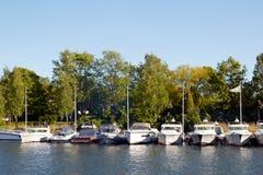 Petits bateaux dans une ligne près des arbres Photographie stock