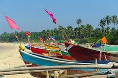 Petits bateaux de pêche dans des couleurs de reggae sur le bord de la mer de plage d'océan contre le ciel bleu L'Inde, Goa, mah image libre de droits