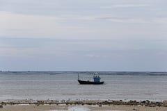 Petits bateaux de pêche en bord de la mer de côte sur la marée basse et le ciel de temps Photo libre de droits