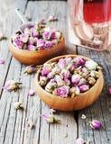 Petits bourgeons secs des roses, thé, karkade, dans des cuvettes en bois, foyer sélectif Image stock