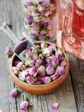 Petits bourgeons secs des roses, thé, karkade, dans des cuvettes en bois, foyer sélectif Photos libres de droits