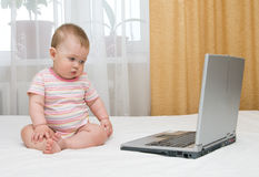 Petits chéri et ordinateur portatif sur le bâti Image stock