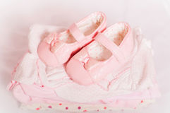 Petits chaussures de bébé et vêtements roses de bébé Image libre de droits