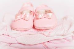 Petits chaussures de bébé et vêtements roses de bébé Photographie stock