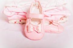Petits chaussures de bébé et vêtements roses de bébé Photographie stock libre de droits