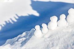 Petits chiffres de bonhommes de neige se tenant sur un sommet de montagne Photographie stock libre de droits