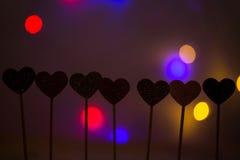 Petits coeurs dans une rangée, lumières à l'arrière-plan Images stock