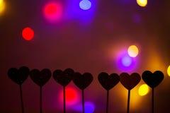 Petits coeurs dans une rangée, lumières à l'arrière-plan Image libre de droits