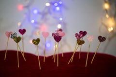 Petits coeurs dans une rangée, lumières à l'arrière-plan Photo libre de droits