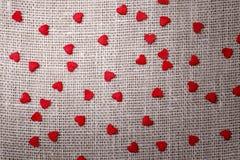 Petits coeurs rouges sur le tissu de toile Photographie stock libre de droits