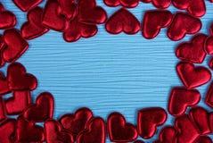 Petits coeurs rouges sur un fond de papier bleu Photos stock