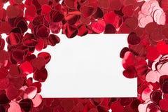 Petits confettis rouges et grands coeurs sur le fond blanc Photos stock