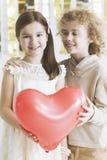 Petits couples tenant le coeur rouge Image stock