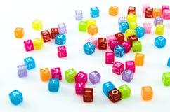 Petits cubes colorés avec aléatoire de caractères dispersé de la fiole d'isolement sur le fond blanc Images stock