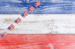 Petits drapeaux des Etats-Unis dans la formation en hausse sur les conseils rustiques avec la nation Photo stock