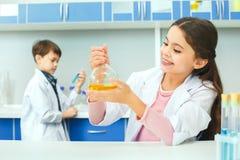 Petits enfants apprenant la chimie dans l'étude de laboratoire d'école Photos libres de droits