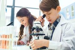 Petits enfants apprenant la chimie dans l'expérience de microscope de laboratoire d'école photographie stock